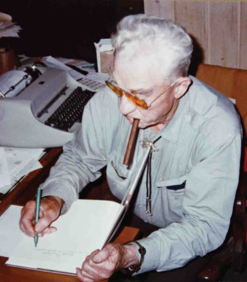 Elmer Keith, with his ever-present cigar, autographing one of his books.