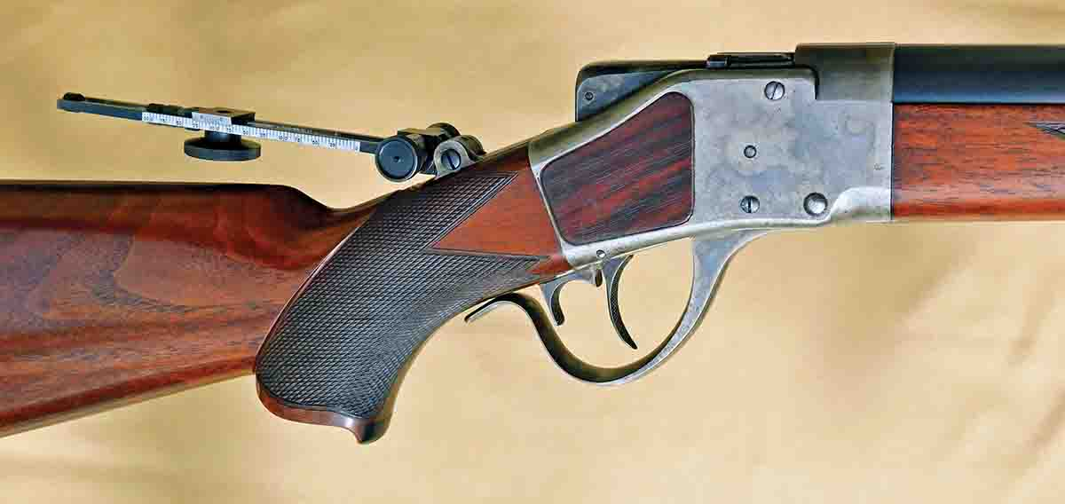 Action area of the Sharps Long Range rifle showing the adapted rear sight stem, faux rosewood action inserts, ebony pistol grip insert and excellently executed checkering.